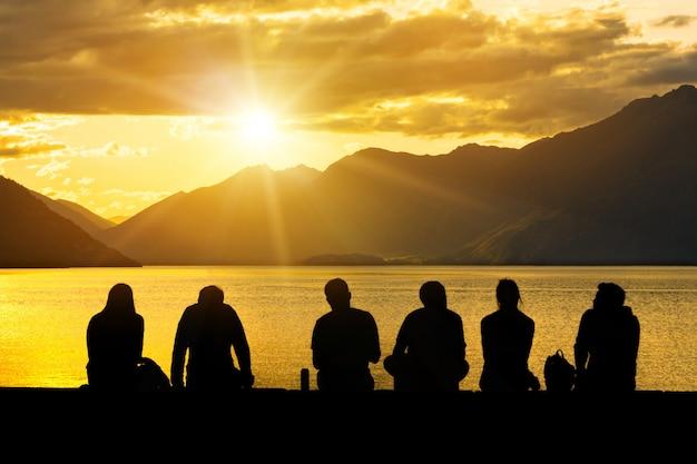 Grupo de silueta de jóvenes sentados en la playa