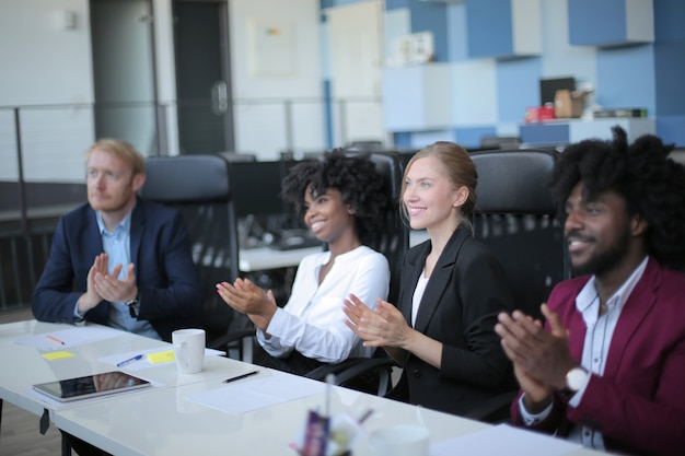 Grupo de socios comerciales diversos exitosos que tienen una reunión de negocios en una oficina moderna