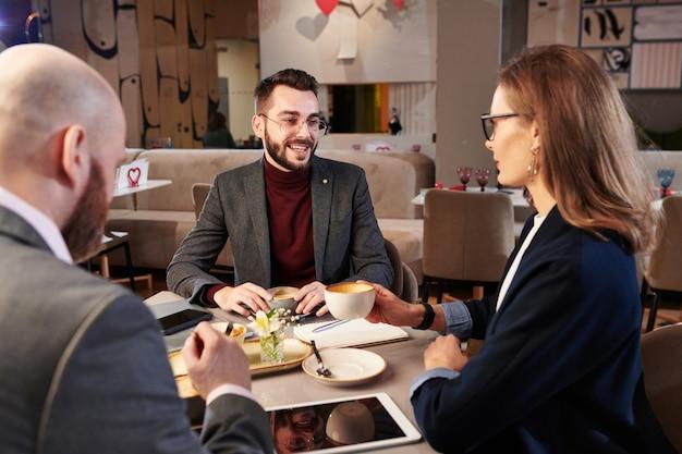 Grupo de socios comerciales modernos tomando café y discutiendo una nueva campaña para aumentar las ventas