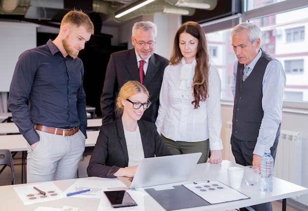 Grupo de socios comerciales que miran asombrosamente la pantalla del portátil
