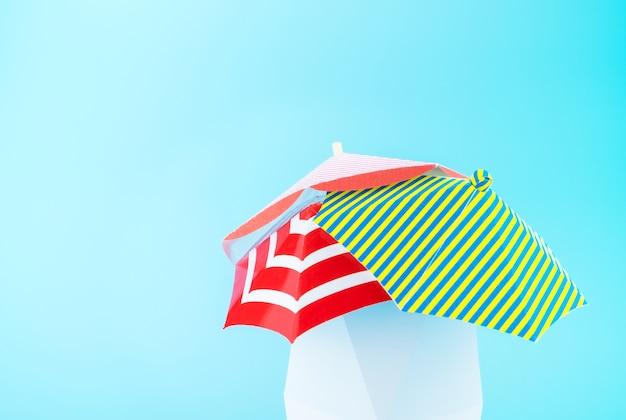 Grupo de sombrilla de playa colorida en caja moderna blanca sobre fondo azul claro