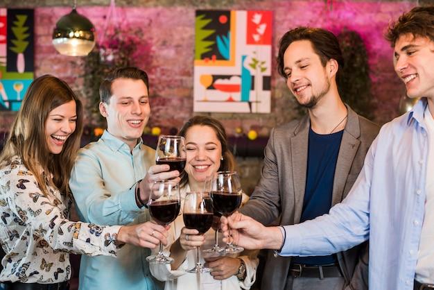 Grupo de sonrientes amigas y amigos brindando vino en un club