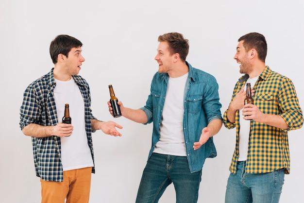 Grupo de sonrientes tres amigos varones disfrutando de la cerveza