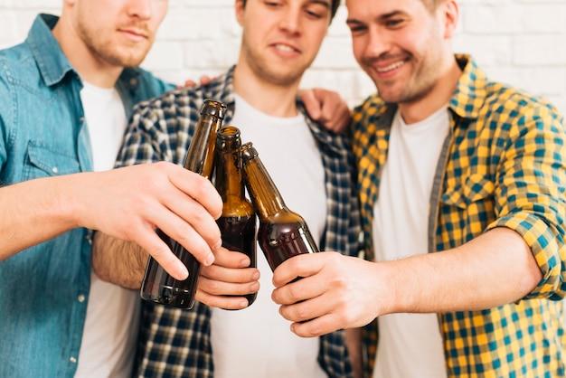 Grupo de sonrientes tres amigos varones tintineando la botella de cerveza