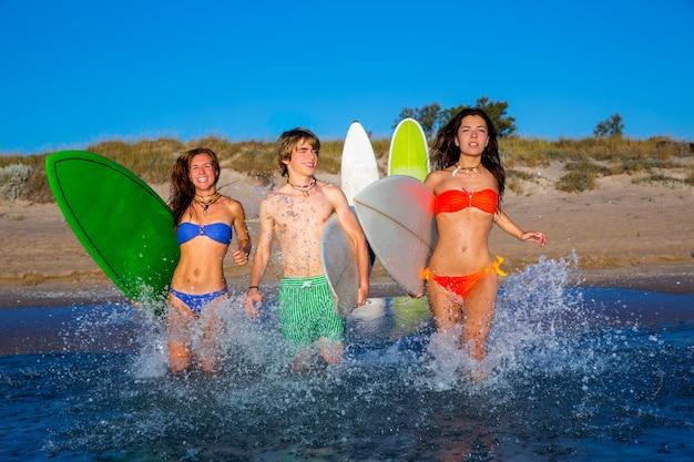 Grupo de surfistas adolescentes corriendo salpicaduras de playa