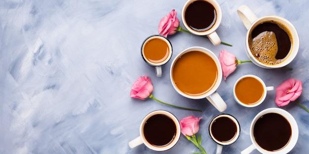 Grupo de tazas y de tazas de café y de flores rosadas en fondo azul. bodegón plano.