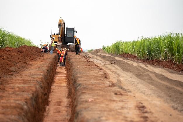 Grupo de trabajador y el ingeniero de la construcción usan drenaje uniforme de agua de excavación de seguridad
