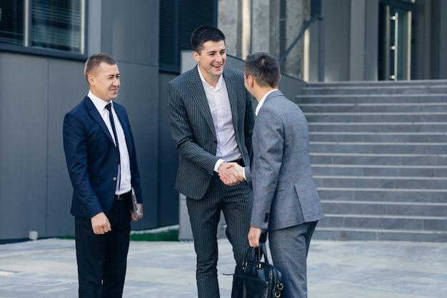 Grupo de trabajadores corporativos de hombres felices saludándose dándose la mano comenzando su día de trabajo en el distrito de negocios contemporáneo.