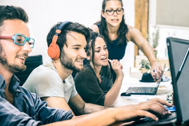 Grupo de trabajadores empleados jóvenes con computadora en estudio de inicio