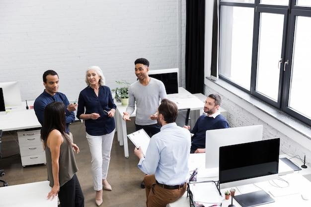 Grupo de trabajadores de oficina discutiendo ideas de negocio