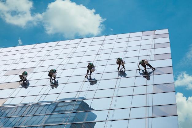 Grupo de trabajadores que limpian el servicio de ventanas en el edificio alto