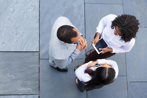 Grupo de trabajadores seguros hablando al aire libre