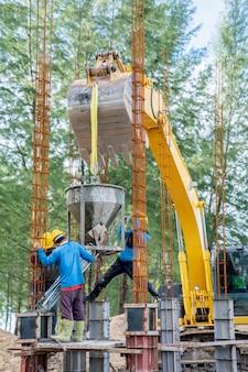 Grupo de trabajadores vertiendo un concreto en el sitio de construcción