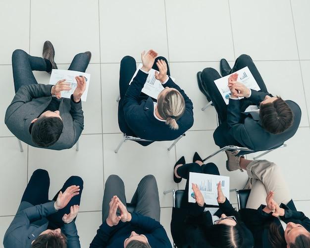 Grupo de trabajo aplaudiendo en una reunión de negocios