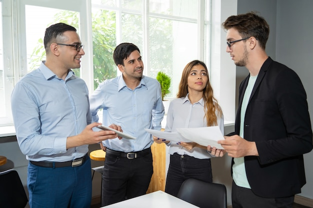 Grupo de trabajo de tres que informan a un líder de equipo joven serio