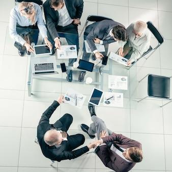 Grupo de trabajo de vista superior analizando estadísticas financieras