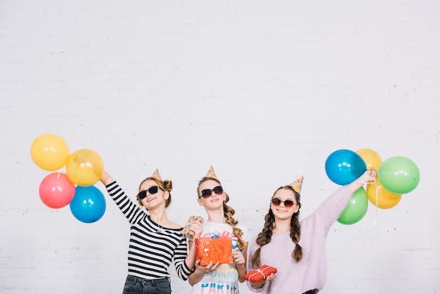 Grupo de tres amigas disfrutando de la fiesta con regalos y globos.