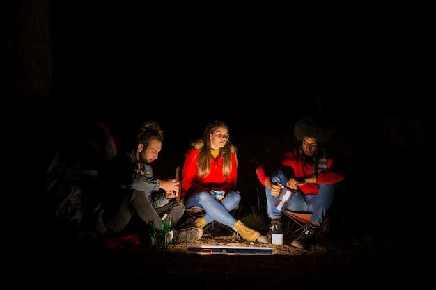 Grupo de tres amigos acampando en el bosque con luz led por la noche