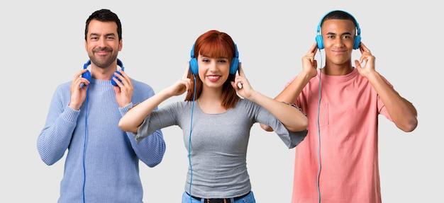 Grupo de tres amigos escuchando música con auriculares.
