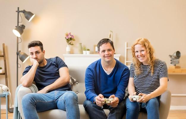 Grupo de tres amigos que juegan videojuegos en casa