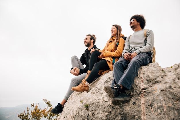 Grupo de tres amigos sentados en la cima del pico de la montaña mirando la vista