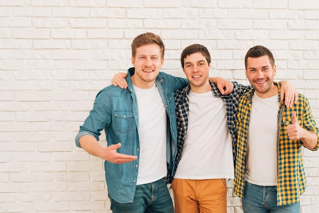 Grupo de tres amigos varones de pie juntos contra la pared blanca