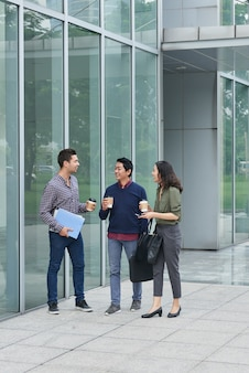 Un grupo de tres colegas caminando al aire libre con café para llevar en un almuerzo