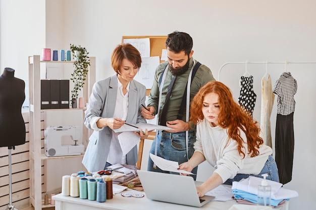 Grupo de tres diseñadores de moda que trabajan en el atelier con laptop y papeles