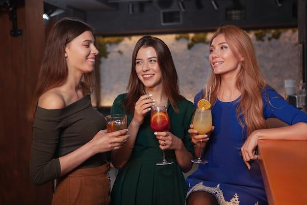 Grupo de tres hermosas mujeres jóvenes conversando sobre bebidas en el bar