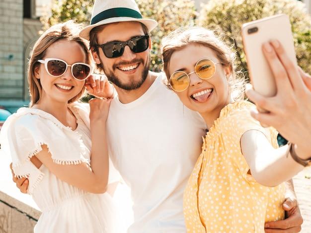 Grupo de tres jóvenes amigos con estilo en la calle. hombre y dos chicas lindas vestidas con ropa casual de verano. modelos sonrientes divirtiéndose en gafas de sol. mujeres y hombres haciendo fotos selfie en teléfono inteligente