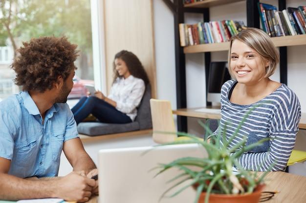 Grupo de tres jóvenes apuestos estudiantes multiétnicos sentado en la biblioteca de la universidad. chico de piel oscura mirando a su amigo leyendo un artículo. chica de pelo claro con cara feliz