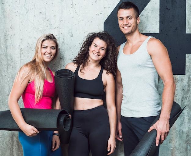 Grupo de tres jóvenes felices con alfombra de fitness
