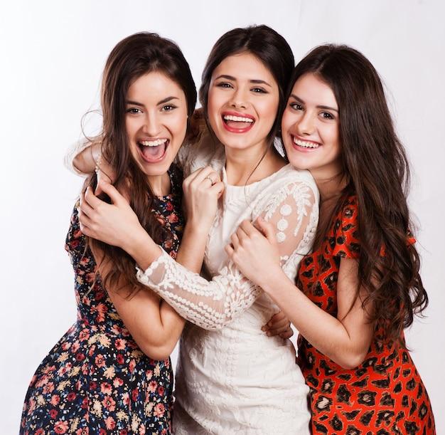 Grupo de tres mujeres felices jóvenes atractivas, hermosas. aislado en blanco