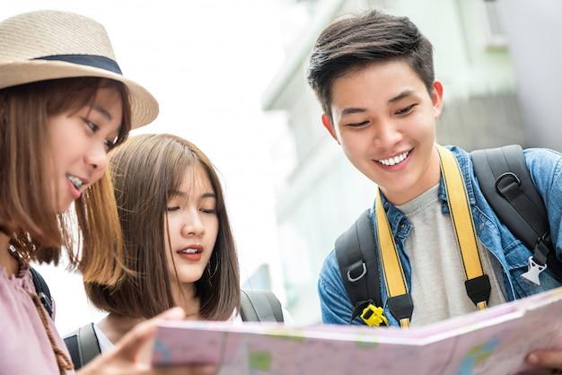 Grupo de turistas amigos asiáticos que buscan dirección en el mapa