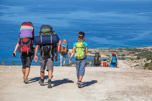 Un grupo de turistas con grandes mochilas camina por un camino de tierra con vistas al mar mediterráneo, la isla de chipre