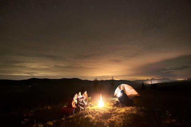 Grupo de turistas con guitarra quemando hoguera bajo el oscuro cielo estrellado con la constelación de la vía láctea.