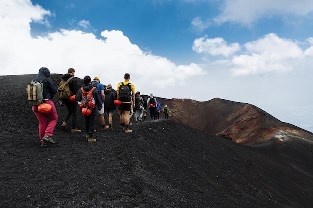 Grupo de turistas que caminan encima del volcán de etna en sicilia, italia