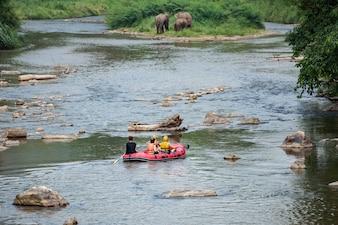 Un grupo de turistas que se divierten en el agua blanca que transporta en balsa en el río de mae taeng. tailandia.