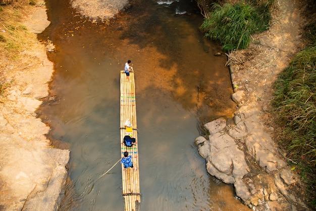 Grupo de turistas que visitan y se sientan en la balsa de bambú flotando en balsa y remando en los rápidos