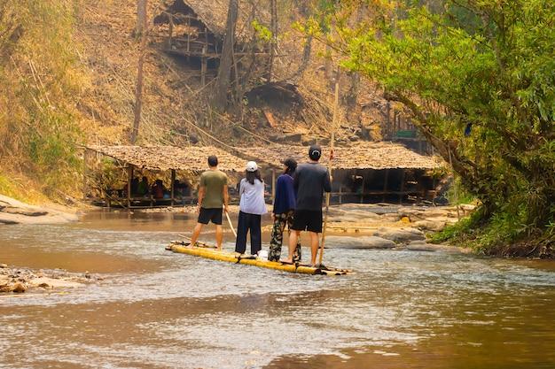 Grupo de turistas que visitan y se sientan en la balsa de bambú flotando en balsa y remando en los rápidos.