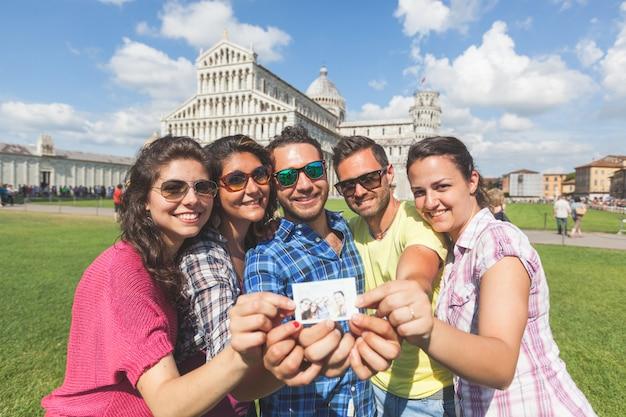 Grupo de turistas con su foto en pisa.