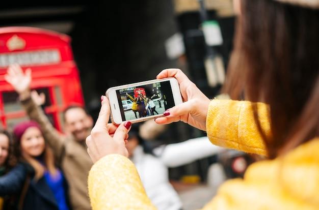 Un grupo de varios amigos toma una foto en una cabina telefónica roja en una calle de londres