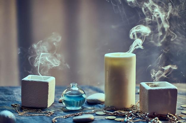 Grupo de velas mágicas de humo y una poción de elixir de botella para un adivinación hechizo oculto ritual de brujería y terrorífico rito de halloween
