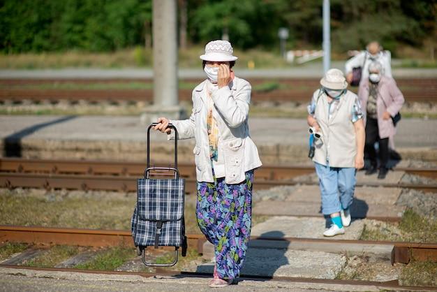 Un grupo de viajeros mayores con máscaras en el rostro cruzan las vías del tren.