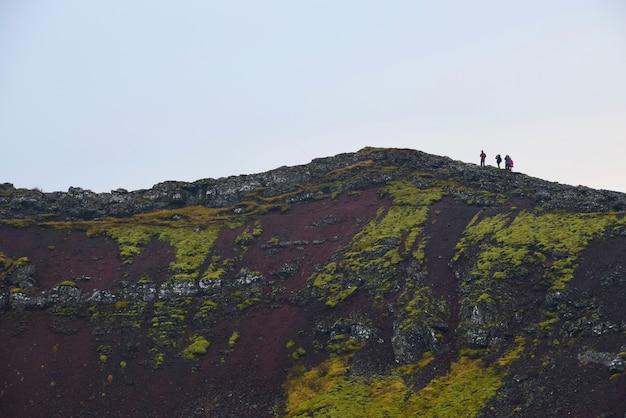 Grupo de viajeros que sube al borde del lago del cráter en islandia.