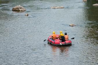 Grupo de viajeros en el rafting inflable en el río, deporte extremo y divertido