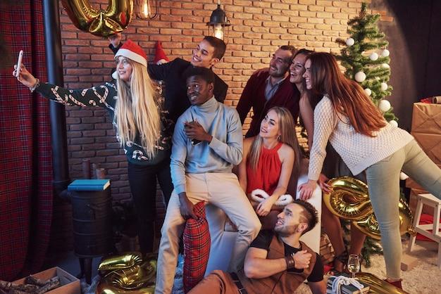 Un grupo de viejos amigos se comunican y hacen una foto selfie. se acerca el año nuevo. celebra el año nuevo en un ambiente hogareño acogedor