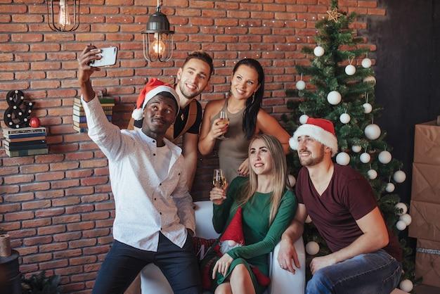 Grupo de viejos amigos se comunican entre sí y hacen una foto de navidad.