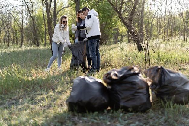 Grupo de voluntarios limpia el parque de escombros. tres personas en la primavera recogen desechos plásticos. concepto de contaminación ambiental