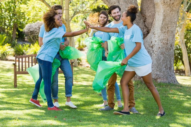 Grupo de voluntarios que se divierten mientras recogen basura